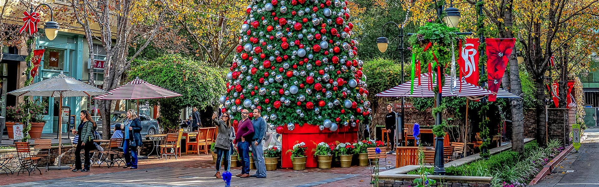 People pose for selfie in front of giant outdoor Christmas tree at open-air mall.